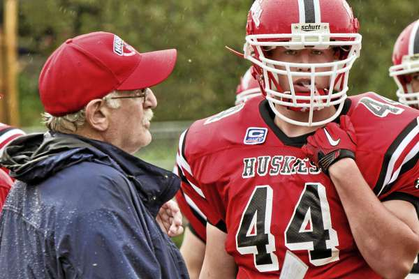 Huskie Coach and League President  Stu Wyckoff talks with  Huskie player Trey Stewart.during a time out in Saturdays game agaisnt the Houlton Knights at SIncock Field in Caribou. the Knights won 41-6.