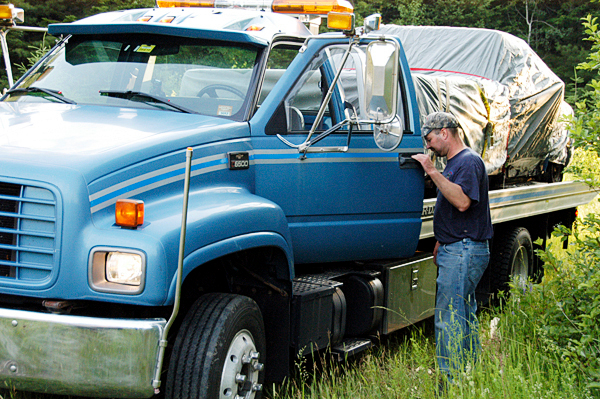 The pickup truck missing since three people were found dead, victims of an apparent triple homicide, in an Amity trailer on Wednesday is carried on a flatbed truck away from a clearing in Weston on Saturday. (Bangor Daily News/ Nick Sambides Jr.)   (WEB EDITION PHOTO)