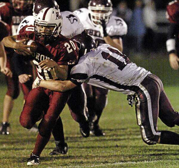 JASON P. SMITH. . . . Orono High School's Dominic Mowrer attempts to break the tackle of Maine Central Institute's Adam Ogden during their game at Orono High School on Friday, September 10, 2010.