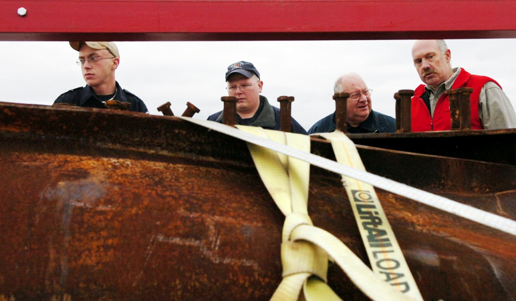 Orrington firefighters (from left) Brian Cochrane, Gerg Spencer and Ron Hamlin and Nickerson & O'Day project manager Walter Shannon (right) take a look at steel beams from New York's World Trade Center that arrived at their permanent home at the new Brewer Public Safety Building.  (BANGOR DAILY NEWS PHOTO BY BRIDGET BROWN)