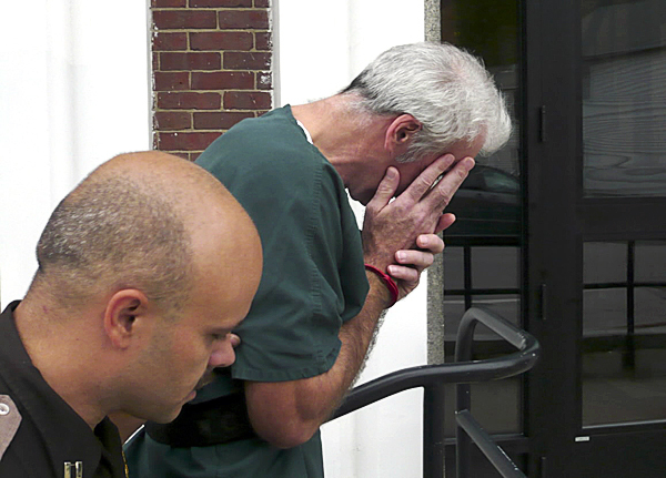 Accused killer Michael Littlefield of Brooks shields his face while being escorted to Waldo County Superior Court by Corrections Officer Robert Walker Friday. Littlefield, 48, entered a plea of not guilty in the June 25 shooting death of his wife Deborah Littlefield, 49, in the kitchen of their home on Veterans Highway. (Walter Griffin photo)