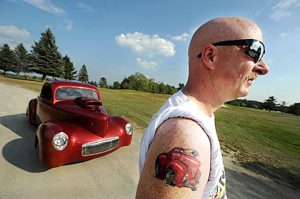 Bruce Johnson of Greenfield poses with his 1941 Willys Coupe on Thursday, September 2, 2010. Johnson loves his car so much that he had a cartoon of it tattooed on his arm. (Bangor Daily News/Kevin Bennett)
