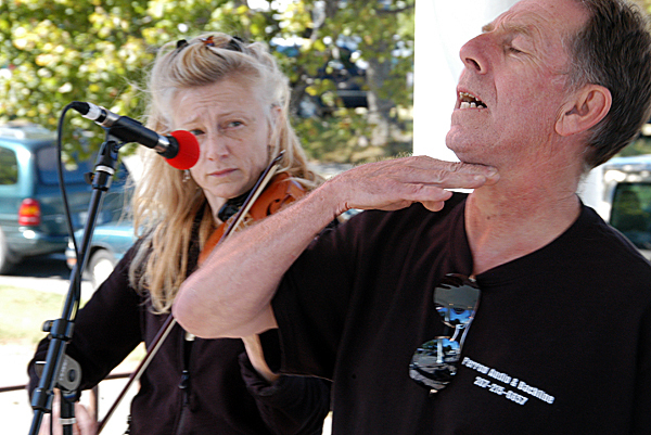 Volunteer Scott Perrow gives the cut sign while he tries to fix an audio problem as violinist Susan Ramsey stands by to play during the Trails End Festival of Millinocket on Saturday.  BANGOR DAILY NEWS PHOTO BY NICK SAMBIDES JR.