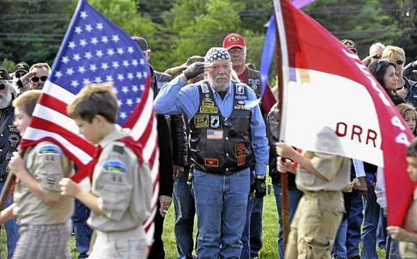 Vietnam War Army veteran Steve &quotScrape&quot  Spooner, center, of Auburn and other members of the Combat Veterans Motorcycle Association saluted the U.S. flag as Boy Scout Troop 44 of Orrington performed color guard duties during the association's wreath-laying ceremony Saturday morning at the Cole Family Land Transportation Museum in Bangor to honor those who died in the attacks on September 11, 2001.