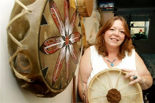In this Sept. 10, 2010 photo, Dawn Macie poses with some of her Abenaki drums in Rutland, Vt. A new state law gives the Vermont Commission on Native American Affairs a process for recommending tribal recognition, which the Abenaki hope will allow them to sell their crafts as Native American and seek federal funding for education and other benefits.  Under federal law, artisans must be members of state- or federally recognized tribes, or be certified as nonmember Indian artisans by a tribe, to sell their wares as Indian-made. The Vermont law sets up a process for tribes to be recognized by showing that they meet certain criteria. (AP Photo/Toby Talbot)