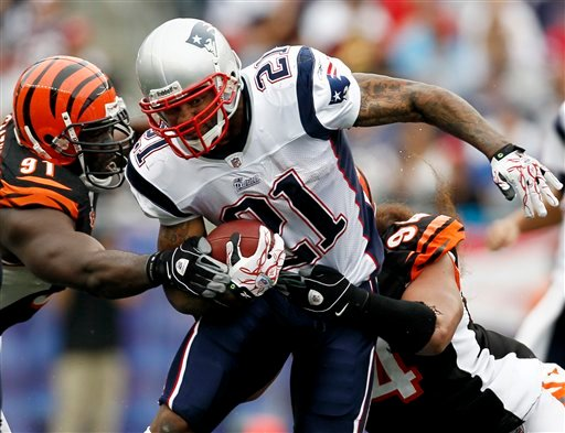 New England Patriots running back Fred Taylor (21) tries to break away from Cincinnati Bengals defensive end Robert Geathers (91) and defensive tackle Domata Peko during the second half of New England's 38-24 win in an NFL football game in Foxborough, Mass., Sunday, Sept. 12, 2010. (AP Photo/Winslow Townson)