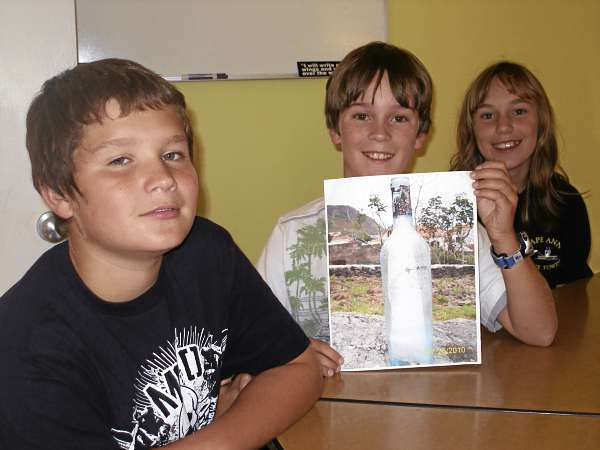 Dustin Colson, a seventh grader at the Adams School in Castine, left, and sixth-graders Liam Griffith and Hannah Flood display a photograph of a bottle that was dropped in the ocean in 2008 and found on a beach in the Azores off the coast of Portugal this summer. The bottle contain messages from the three students which they sent as part of a school-wide project, several of which have been recovered a points around the Atlantic Ocean.  BANGOR DAILY NEWS PHOTO BY RICH HEWITT
