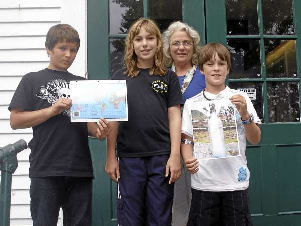 Dustin Colson, a seventh grader at the Adams School in Castine, left, and sixth-graders Liam Griffith and Hannah Flood, along with teacher Cheryl McFadden, display a world map and a photograph  of a bottle that was dropped in the ocean in 2008 and found on a beach in the Azores off the coast of Portugal this summer. The bottle contain messages from the three students which they sent as part of a school-wide project, several of which have been recovered a points around the Atlantic Ocean. BANGOR DAILY NEWS PHOTO BY RICH HEWITT