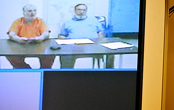 Robert Strout, left, of Orient appeared with his attorney, Jeffrey Pickering, via video conferencing from the Aroostook County Jail in Houlton, in Maine District Court in Presque Isle Monday morning, September 13, 2010. Police arrested Strout on Friday and charged him in connection with the triple homicide in Amity in June. (Bangor Daily News/John Clarke Russ)