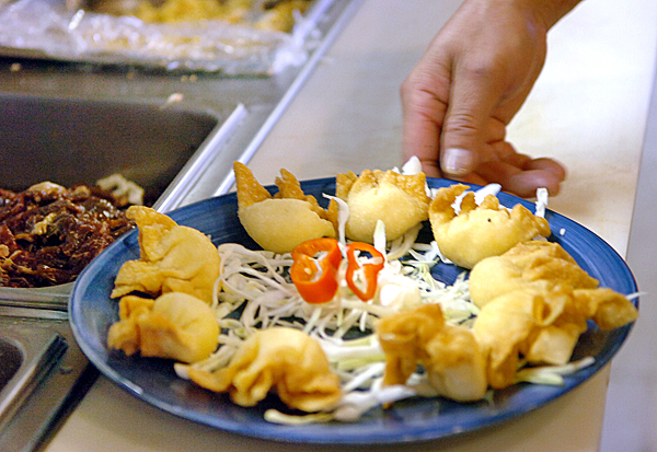 (BANGOR DAILY NEWS PHOTO BY BRIDGET BROWN)CAPTIONWowWee Hawaiian BBQ owner and cook Ken Wong puts the finishing garnishes on a crab rangoon appetizer Friday, Sept. 10, 2010 in Brewer. (Bangor Daily News/Bridget Brown)