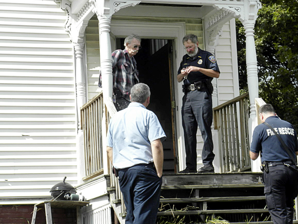 Hampden Police Chief Joe Rogers, top step on right, collects information from building maintenance man John Frost, top left, and Suburban Propane technician Steve Charette, bottom left, who both discovered a body Tuesday afternoon in a Hampden apartment building on the Main Road. Hampden Fire Department fire inspector Keith Barnhard is at the bottom right. Bangor Daily News photo by Nok-Noi Ricker