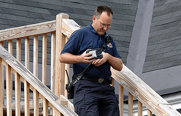 Keith Barnhard, fire inspector for Hampden Fire Dept., walks down an apartment house exterior stairway as he uses a gas detection device after a resident was found dead in his apartment Tuesday, Sept. 14, 2010. (Bangor Daily News/Scott Haskell)