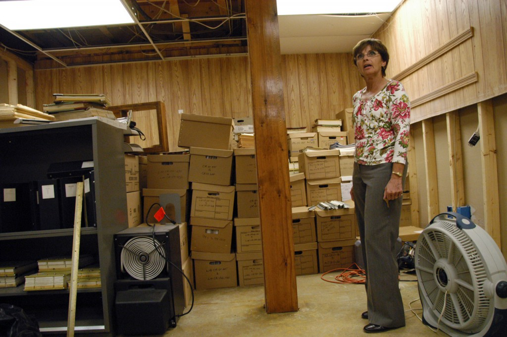 Sharon Webster, clerk of the court at Lincoln District Court, stands Wednesday among some of the dozens of boxes of old court files clerks raced to save when the courthouse building was flooded by a malfunctioning toilet earlier this month. BANGOR DAILY NEWS PHOTO BY NICK SAMBIDES JR.