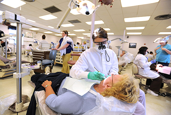 Dental student Kayla Haninston cleans Patricia Cerini's teeth, part of students' dental education at University College of Bangor. The college will be spending $3 million dollars to move and expand the Dental Health Clinic which suffers from a lack of privacy cubicles and aging equipment. (Bangor Daily News/Kevin Bennett)