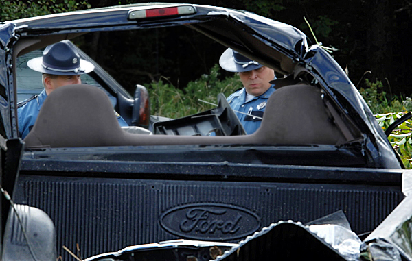 Maine State Police Troopers Darren Vittum, left, and Forrest Simpson examine the wreckage of a pickup truck, one of two vehicles involved in a double rollover accident on Route 9 in Newburgh on Thursday afternoon, Sept. 16, 2010.  The pickup truck had been pulled into an upright position just before they looked it over. (Bangor Daily News/Scott Haskell)