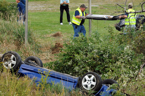 Wayne Bouchard, left, and Peter Roach, from Bouchard & Sons Towing, move the tailgate of a wrecked pickup truck, one of two vehicles involved in a double rollover accident on Route 9 in Newburgh on Thursday afternoon, Sept. 16, 2010.  (Bangor Daily News/Scott Haskell)