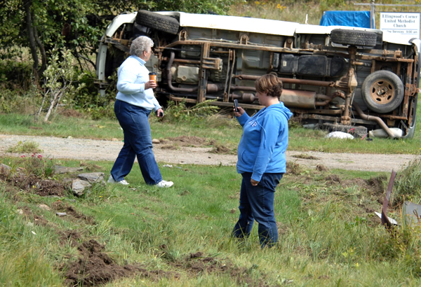 Elizabeth Deane, foreground, checks a photo she took with her phone of the pickup truck that skidded and rolled over,ejecting the driver on her Monroe Road lawn before the vehicle came to rest on its side in Winterport Thursday morning, Sept. 16, 2010. Also checking out the scene is her mother-in-law Mary Lou Deane.  Waldo County Sheriff's Office is investigating the accident, which was about 100 yards from the intersection of Route 69 at Ellingwood's Corner.  The driver was transported to the hospital by Hampden Fire Dept. ambulance.  Winterport Fire Dept. rescue units also responded to the scene. (Bangor Daily News/Scott Haskell)
