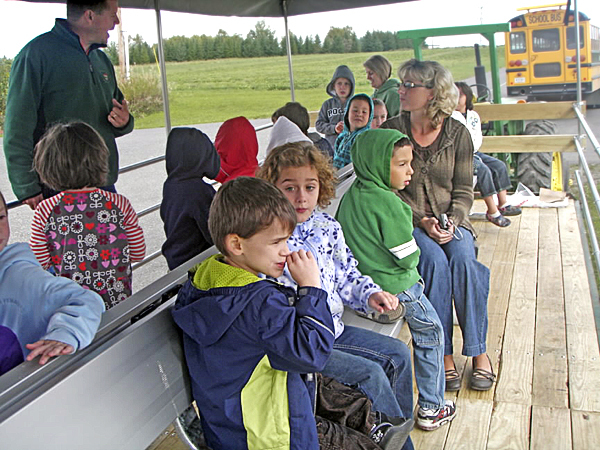 AARON BUZZA, left, SAD 1 Educational Farm manager, leads Jennifer Espling?s and Kelli Beaulieu?s first-grade classes at Pine Street Elementary School on a tour of the school farm Monday. The school farm received a $4,400 Maine Agriculture in the Classroom grant to make modifications to the 8-foot by 26-foot trailer that?s used to showcase the facility. A canopy, secure seating system and railing have been added to make the trailer safer and more suitable for all types of weather. New access stairs will eventually be added, as well. The grant funding was made possible through the sale of the state?s agriculture license plates. Photo courtesy of the Presque Isle Regional Career and Technical Center