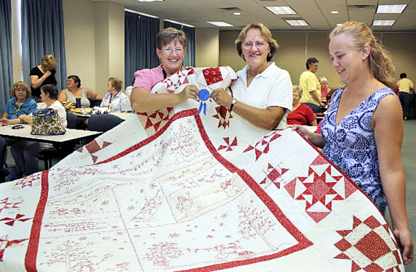 CONGRATULATIONS ? Joyce Fitzpatrick, left, hands first-place ribbon to Sandra P. Henderson of Littleton for her red and white quilt. It was entered in the Friends and Needles Quilt Guild show?s small-size category. Addie Boyett, right, of Amity counted the votes. Houlton Pioneer Times Photo/Elna Seabrooks
