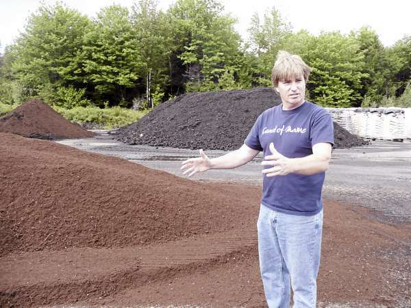 Cameron Bonsey, marketing director of Coast of Maine, explains the mixing and aging process of the company's compost and garden products at the Marion Township facility. Using waste products - lobster shells, blueberry and salmon waste, bark, and cow manure from Aroostook County feedlots - the company is making a value-added product that is now carried by more than 700 independent garden centers on the East Coast. BANGOR DAILY NEWS PHOTO BY SHARON KILEY MACK