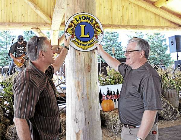 Fort Kent Lions Robert Johnson (left) and Stephen Gagne fly their colors before the club officially dedicated the new Lions' Den Pavilion in Fort Kent's Riverside Park. The $250,000 structure is the largest project in the club's 72-year history. (Bangor Daily News/Julia Bayly)