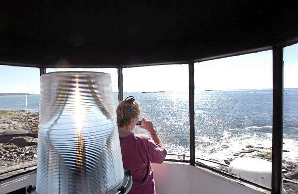 Kathy Doucette of East Bridgewater, Mass. takes in the view from inside Marshall Point Lighthouse in St. George on Saturday morning, Sept. 18, 2010 as part of the second annual Maine Open Lighthouse Day. The light station at Marshall Point dates back to 1831 and was last operated by a lightkeeper in 1971 when it was automated. The lighthouse now belongs to the Town of St. George while the Coast Guard is in charge of operating the light and fog horn. (Bangor Daily News/Bridget Brown)