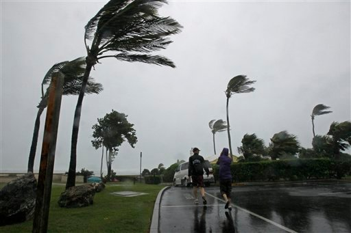 A couple walks near Elbow Beach in Paget Parish as Hurricane Igor moves onto Bermuda, Sunday, Sept. 19, 2010. (AP Photo/Gerry Broome)