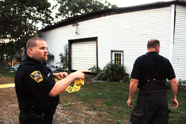 Brewer police Officer Jeff Gotreau, left, and Firefighter Bill Reaviel (cq) set up a perimeter around an old warehouse where the roof was reportedly caving in Monday night, Sept. 20, 2010, between Union and Parker streets in Brewer near the railroad tracks. BANGOR DAILY NEWS PHOTO BY SCOTT HASKELL