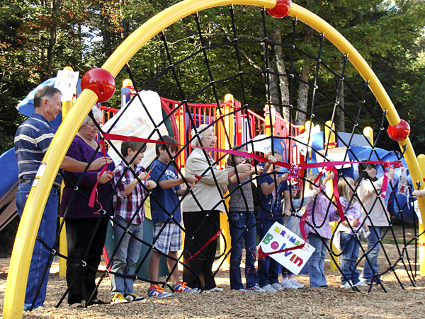 Jim and Susan Larson of Brownville, left, and Honorene Richardson of  Brownville, joined Brownville Elementary children in cutting the ribbon  Monday to the new $45,000 playground at the school. Parents, students,  local organizations and businesses, along with donations in memory of  Richardson's late husband, George; the Larson's son Andrew; and the late  Donna Paul, along with a grant made the new playground possible. (Bangor  Daily News Photo by Diana Bowley)