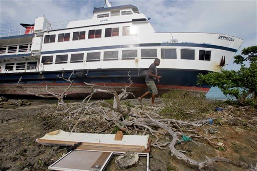 A man walks by the excursion boat &quotBermudian&quot after it broke loose and was pushed to shore by Hurricane Igor in St. George, Bermuda, Monday, Sept. 20, 2010. (AP Photo/Gerry Broome)
