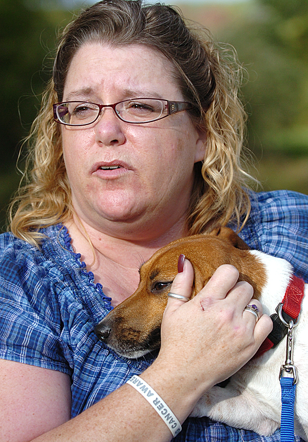 &quotI was in [the apartment] and kept hearing the fire alarm go off, so I went out in the hallway and saw smoke and called 911,&quot said Karen Sasso while comforting her dog, Hoagie, after escaping the fire at her 33 Hampden Road home in Carmel on Tuesday.   BANGOR DAILY NEWS PHOTO BY BRIDGET BROWN