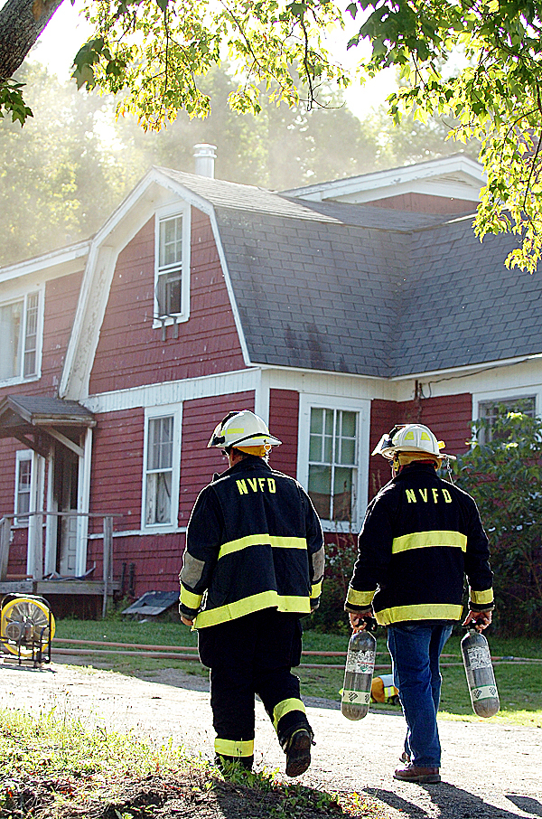 Newburgh Fire Department Chief Glen Williamson (left) and Assistant Chief Keith Miller bring extra air packs to fellow firefighters at the scene of a house fire at 33 Hampden Road in Carmel on Tuesday, Sept. 21, 2010. No one was injured in the fire   BANGOR DAILY NEWS PHOTO BY BRIDGET BROWN