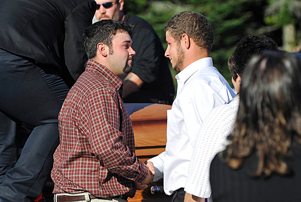 William Gray, left, is consoled by a loved one as he stands near the casket of his daughter, MacKenzie Renae Gray, which was put in the bed of a pickup truck after Tuesday's funeral service for Carlos Tapia , Carlos' wife Rachelle Renae Parker and  MacKenzie Renae Gray at Beals Elementary School. Their tragic death in a traffic accident last week has left the community in mourning. BANGOR DAILY NEWS PHOTO BY JOHN CLARKE RUSS