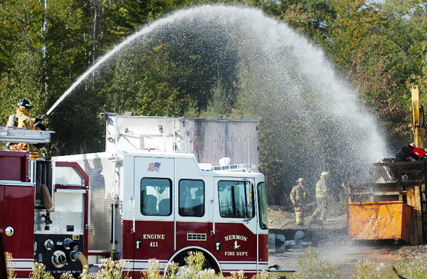 Firefighters douse a dumpster at the scene of the first of two afternoon fires in Carmel on Tuesday, Sept. 21, 2010. The fire was at a scrap metal business called Deal Recycling Inc. on Main Road in Carmel.  BANGOR DAILY NEWS PHOTO BY BRIDGET BROWN