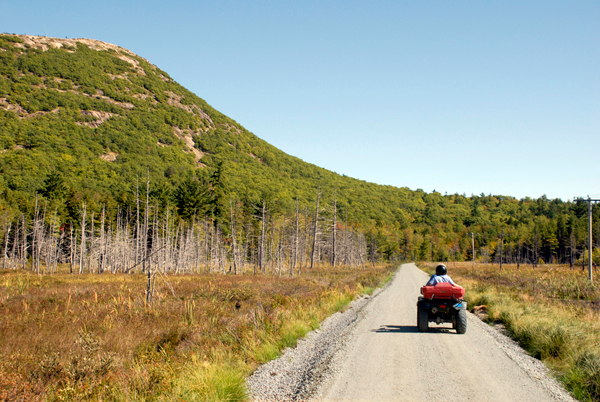 Two ATVers riding on a &quot2-up&quot ATV head east on the Down East Sunrise Trail where it crosses the Schoodic Bog beneath Schoodic Mountain on Saturday, September 18. (Bangor Daily News/Brian Swartz)