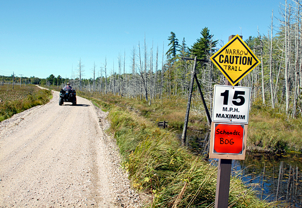 Riding on the Down East Sunrise Trail on Saturday, September 18, an ATVer approaches signs placed at the eastern edge of the Schoodic Bog in Sullivan. BANGOR DAILY NEWS PHOTO BY BRIAN SWARTZ