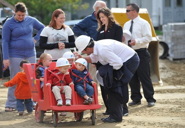 Karl Ward, CEO of Nickerson & O'Day placed hard hats on toddlers in the Bangor Y's Discovery Friends Day Care. Behind him (from left) were day care intern Chelsea Dow, toddler teacher Kristen York, George McHale (obscured), Bangor Y board president Racquel Tibbetts, and Bangor Y CEO Mike Seile. They joined other members of the Bangor Y community to break ground for the new parking lot at the Bangor Y's Second Street location Thursday morning, September 23, 2010. (Bangor Daily News/John Clarke Russ)