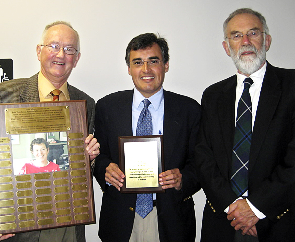 An award named after a Bangor attorney who died in April was presented Wednesday to Cesar Britos, an attorney at UMUM, who is a member of the Pine Tree Legal Assistance Board of Directors. Left to right:  Board President Robert Lingley holds a plaque with Janet Milley's photo on it that will be permanently placed in the Bangor office of Pine Tree Legal; Cesar Britos, award winner; and Douglas Coffin, husband of Janet Milley's. (Photo courtesy of  Hope Hilton)