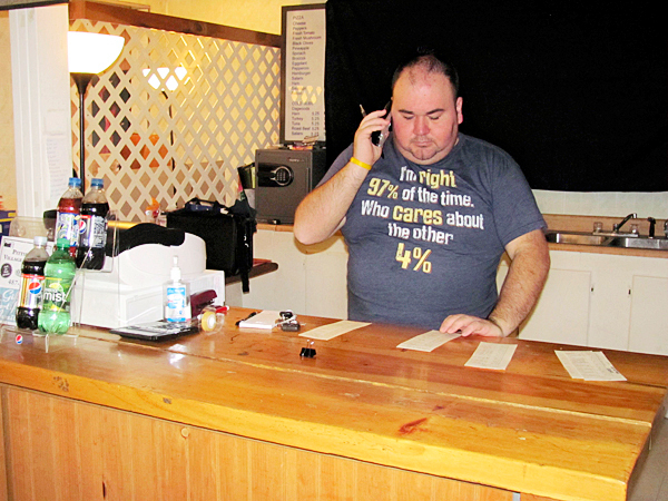 David Rickett of Detroit, who bought Pittsfield Village Pizzeria earlier this month with his partner, David McDonald, communicates payroll information over the phone on Thursday, Sept. 23, 2010. Rickett and McDonald bought the restaurant on Sept. 1 from George and Voula Maniatakos and have made many changes in their first few weeks in business. BANGOR DAILY NEWS PHOTO BY CHRISTOPHER COUSINS   w/&quotnewowners&quot