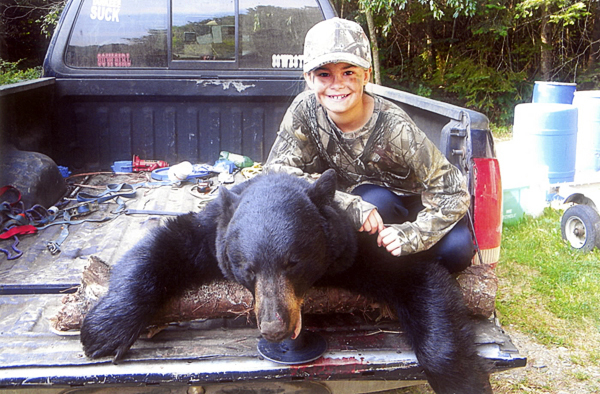 Ashlee Vilasuso of Orrington poses with the 220 pound black bear she shot recently while hunting with her father, Ron. Ten-year-old Ashlee also is a black belt in karate and has won numerous awards in cowboy action shooting competitions. (Photo courtesy of the Vilasuso family)