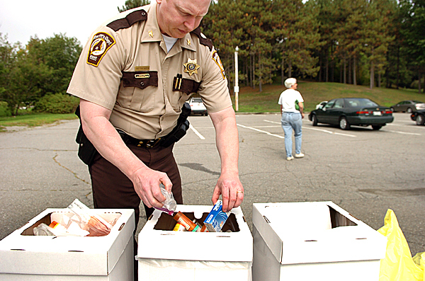 Chief Troy Morton with the Penobscot County Sheriff's Department dispenses drugs into containers which were turned in by community members as part of a national prescription drug take-back campaign at Cascade Park in Bangor on Saturday, Sept. 25, 2010. (Bangor Daily News/Bridget Brown)