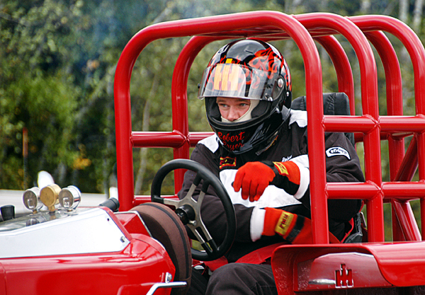 Robert Pryor, a 23-year-old tractor driver from Centerville, New Brunswick, belts himself in before racing in the Northern Timber Cruisers Truck Pull at Millinocket Regional Airport on Saturday.  BANGOR DAILY NEWS PHOTO BY NICK SAMBIDES JR.