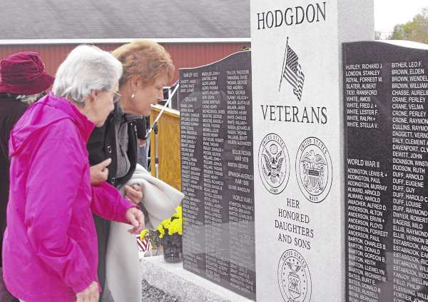 More than 100 people attended a ceremony on Sunday, Sept. 26, to dedicate Hodgdon?s new veterans memorial monument. The new granite memorial, which is located adjacent to the Hodgdon Fire Station, replaces an old wooden memorial that had been located in the downtown. Here, two attendees read the list of names of war veterans dating back to the Civil War and extending to the Vietnam War. (BANGOR DAILY NEWS PHOTO BY JEN LYNDS)