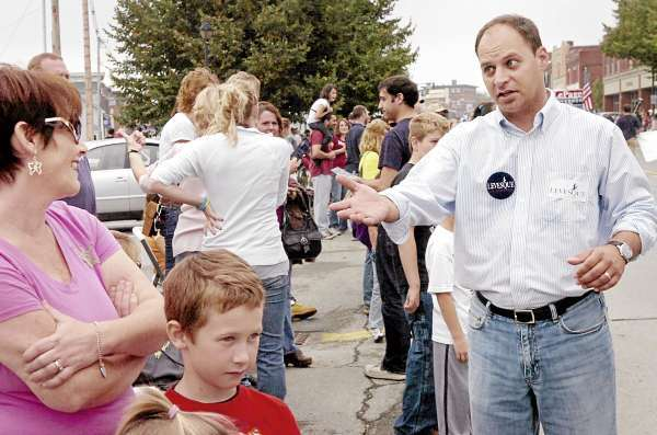 Jason Levesque of Auburn (right), who is challenging Congressman Mike Michaud to represent Maine's 2nd District, talks to voters during Old Town's Riverfest parade on Saturday morning, Sept. 25, 2010. (Bangor Daily News/Bridget Brown)