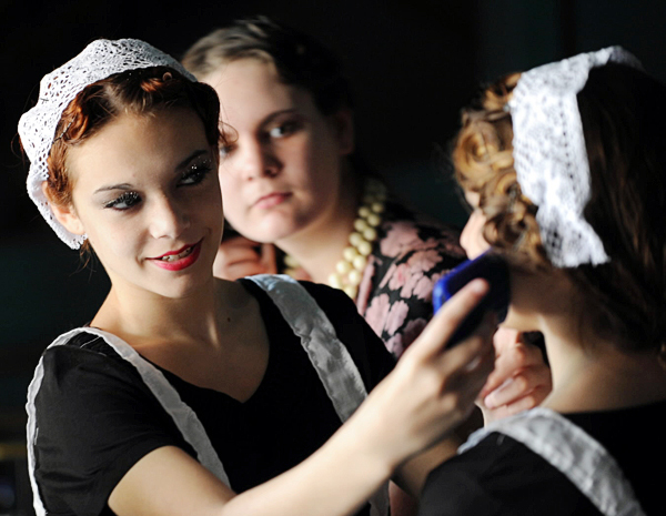 Maxine Buretta, left, holds a smart phone with a picture of actress Marion Cotillard up to see if Clio Berta, right, looks like the movie star as Alice Richardson, center, peeks to see the resemblance. The three were at the Strang Theater on Saturday, September 25, 2010 to be in a music video about the roaring 20's. (Bangor Daily News/Kevin Benett)