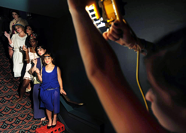 Rockland High School student Hannah Lacasse, right, holds a work light to illuminate high school students dressed in 1920's period costumes during the filming of a music video at the Strang Theater on Saturday, September 25, 2010.(Bangor Daily News/Kevin Bennett)