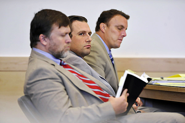 Seated between his defense attorneys Richard Hartley, left, and Peter Cyr, defendant Colin Koehler of Bangor listens to Assistant Attorney General Donald McComber (not pictured) deliver the prosecution's opening arguments and at the start of Koehler's jury trial at Penobscot Judicial Center Monday. Koehler is accused of the stabbing death of 19 year-old Holly Boutilier of Old Town on Bangor's riverfront in August 2009. (Bangor Daily News/John Clarke Russ)