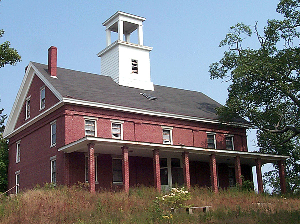 Wilson Hall, a 150-year-old building atop Oak Hill in Bucksport, has fallen into disrepair and town officials are concerned that it poses a safety hazard to the community. The Town Council has called for the owner to secure the building immediately and submit a plan by Sept. 13 to restore it. (NEWS Photo by Rich Hewitt)