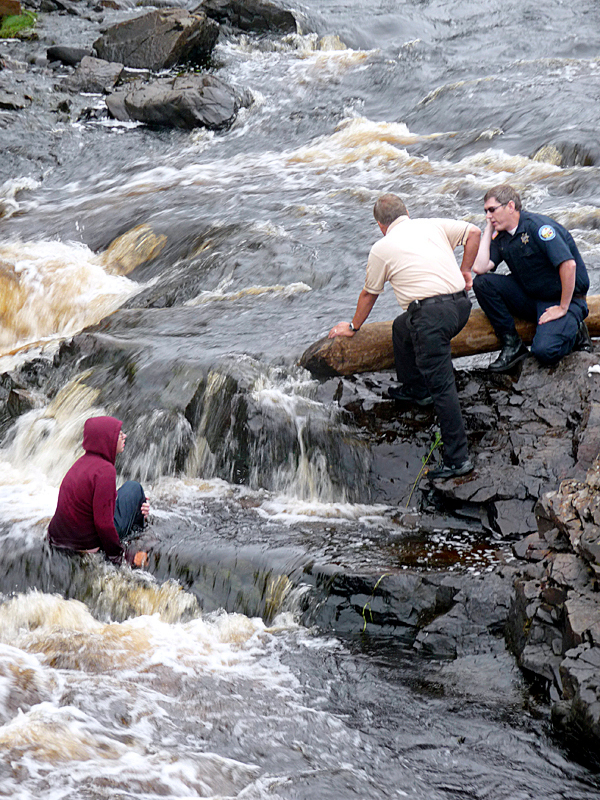 A distraught 15-year-old Jonesport girl had to be forcably retrieved from the cold waters of the Machias River Thursday afternoon by Washington County Sheriff Donnie Smith (center) and Richard Strout of the Machias Police. The girl was the subject of a major search in the Jonesport area on Tuesday and Wednesday after she reportedly ran away from her home, Smith said. Smith found the girl Wednesday afternoon on a Jonesport beach attempting to harm herself and brought her to Down East Community Hospital. Smith said she fled into the river Thursday to avoid a counseling appointment. Smith talked her out of the water once but she then went back in, at times submerging herself to her neck, as she threw large rocks at the sheriff. The girl was in the water nearly two hours before she was grabbed by Smith, who admitted later that he does not know how to swim. Smith and Strout were assisted at the scene by the Machias Fire and Ambulance Service. BANGOR DAILY NEWS PHOTO BY SHARON KILEY MACK