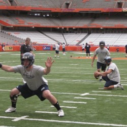 UMaine place-kicker Chris Gennaro practices field goals with the aid of holder Jared Turcotte and snapper Spencer Wood (foreground) during Friday afternoon's practice at the Carrier Dome in Syracuse, N.Y.